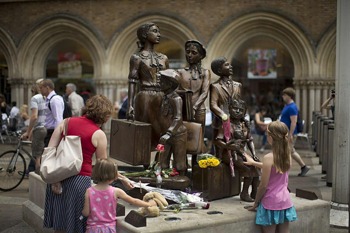 People look at flowers laid in memory of Britain's Sir Nicholas Winton on German-born Jewish sculptor Frank Meisler's