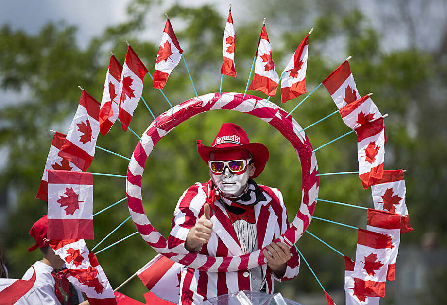 A character on a float gives a thumbs-up along the Canada Day parade route through Port Credit, Wednesday, July 1, 2015, in Mississauga, Ontario. The holiday celebrates the joining of provinces to create Canada in 1867. (Peter Powers/The Canadian Press via AP)
