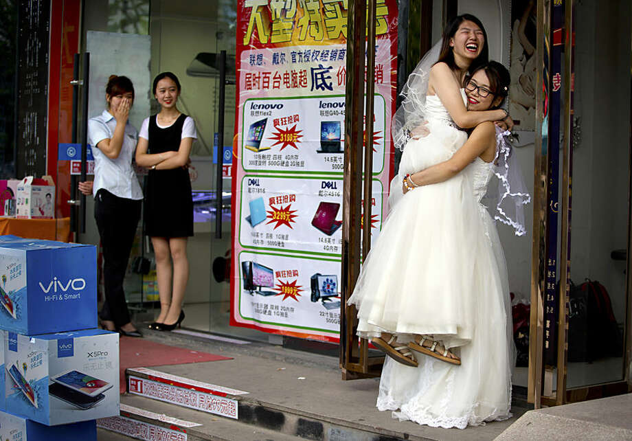 Li Tingting, second from right, laughs as she is lifted off the ground by her wife Teresa Xu, right, outside of a beauty salon where the two were preparing for their wedding as clerks from an adjacent shop look on in Beijing, Thursday, July 2, 2015. A prominent Chinese lesbian couple held a simple ceremony Thursday to announce their informal marriage, in their latest effort to push for legalization of same-sex unions in China. (AP Photo/Mark Schiefelbein)