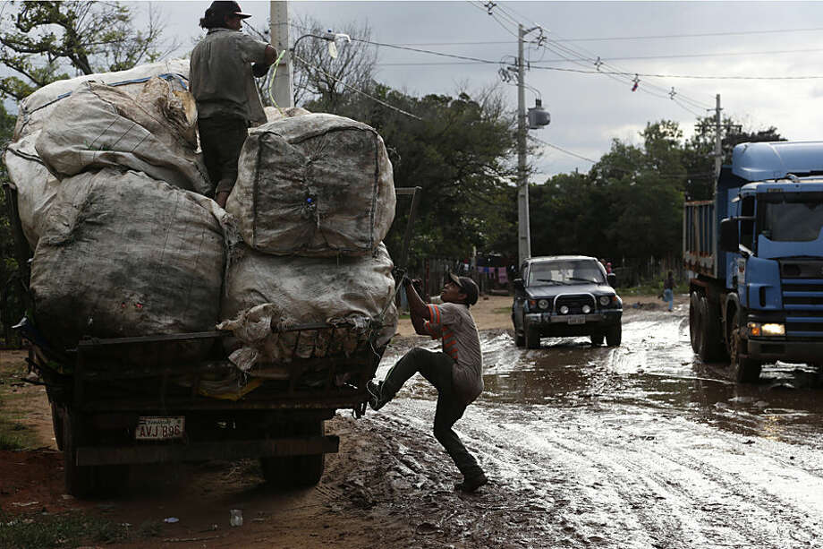 In this May 30, 2015 photo, trash collectors secure a load on their truck in the Banado Norte neighborhood of Asuncion, Paraguay, an area Pope Francis will visit in July. The men work for a recycling depot that collects and sells used aluminum cans, other metals, plastic and cardboard. (AP Photo/Jorge Saenz)