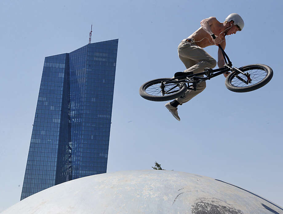 A biker performs a jump in a bike park near the European Central Bank, in rear, in Frankfurt, Germany, Wednesday, July 1, 2015. (AP Photo/Michael Probst)