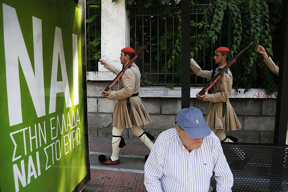Evzones of Greek Presidential Guards walk by an elderly man who waiting the bus at the station with a posters of YES vote in the upcoming referendum, in central Athens, on Thursday, July 2, 2015. Greece braced for more chaos on the streets outside its mostly shuttered banks Thursday, as Athens and its creditors halted talks on resolving the country's deepening financial crisis until a referendum this weekend. (AP Photo/Petros Karadjias)