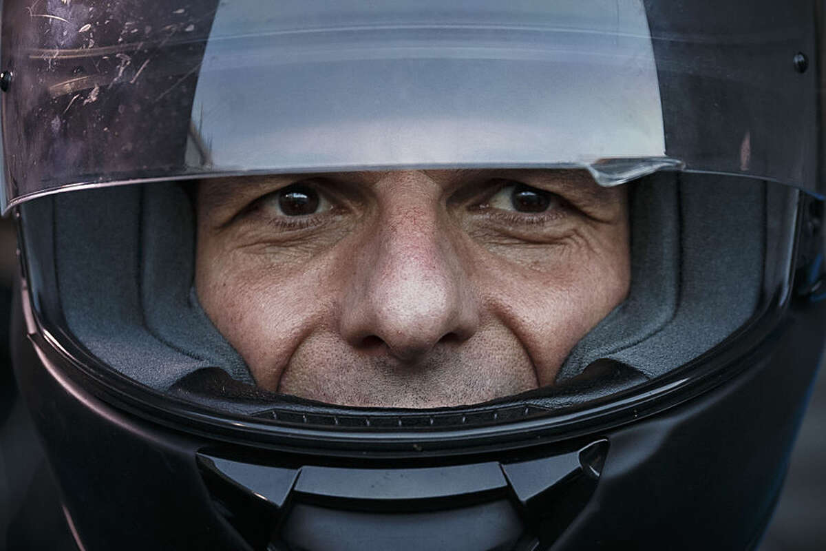 Greece's Finance Minister Yanis Varoufakis puts on his motorbike helmet as he leaves his office in Athens, Wednesday, July 1, 2015. About 1,000 bank branches around the country were ordered by the government to reopen Wednesday to help desperate pensioners without ATM cards cash up to 120 euros ($134) from their retirement checks. Eurozone finance ministers were set to weigh Greece's latest proposal for aid Wednesday. (AP Photo/Daniel Ochoa de Olza)