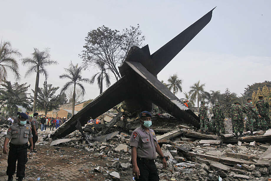 Rescuers search for victims at the site where an Indonesian air force transport plane crashed in Medan, North Sumatra, Indonesia, Wednesday, July 1, 2015. The C-130 Hercules plane crashed into a residential neighborhood in the country's third-largest city on June 30. (AP Photo/Binsar Bakkara)