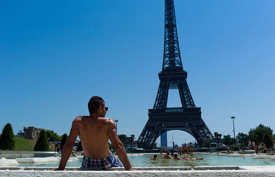 A man relaxes by the fountain of the Trocadero gardens, in front of the Eiffel Tower, in Paris, Wednesday, July 1, 2015. A mass of hot air moving north from Africa has driven up temperatures in Spain, Portugal, Britain and France in recent days. Temperatures in Paris were expected to hit 39 degrees Celsius (102 Fahrenheit) Wednesday afternoon. (AP Photo/Thibault Camus)