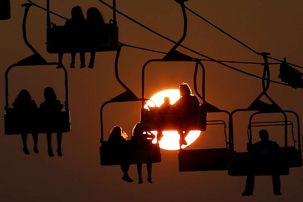 The sun sets behind people on a ride at the State Fair Meadowlands, Wednesday, July 1, 2015, in East Rutherford, N.J. The fair closes on Sunday. (AP Photo/Julio Cortez)