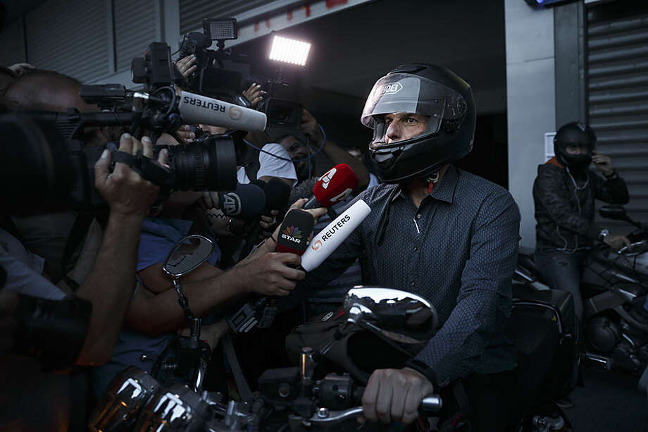 Greece's Finance Minister Yanis Varoufakis answers questions from the media as he prepares to ride his motorbike as he leaves his office in Athens, Wednesday, July 1, 2015. About 1,000 bank branches around the country were ordered by the government to reopen Wednesday to help desperate pensioners without ATM cards cash up to 120 euros ($134) from their retirement checks. Eurozone finance ministers were set to weigh Greece's latest proposal for aid Wednesday. (AP Photo/Daniel Ochoa de Olza)