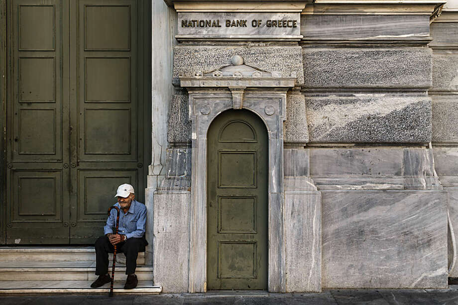 An elderly man waits to be allowed into a bank to withdraw a maximum of 120 euros ($134) for the week, Thursday, July 2, 2015. Greece braced for more chaos on the streets outside its mostly shuttered banks Thursday, as Athens and its creditors halted talks on resolving the country's deepening financial crisis until a referendum this weekend. (AP Photo/Daniel Ochoa de Olza)