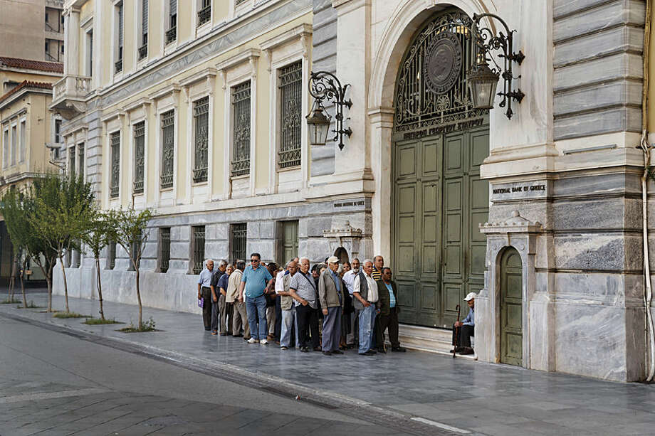 Pensioners line up as they wait to be allowed into a bank to withdraw a maximum of 120 euros ($134) for the week, Thursday, July 2, 2015. Greece braced for more chaos on the streets outside its mostly shuttered banks Thursday, as Athens and its creditors halted talks on resolving the country's deepening financial crisis until a referendum this weekend. (AP Photo/Daniel Ochoa de Olza)