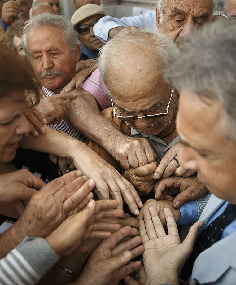 Pensioners try to get a number to enter inside a bank in Athens, Wednesday, July 1, 2015. About 1,000 bank branches around the country were ordered by the government to reopen Wednesday to help desperate pensioners without ATM cards cash up to 120 euros ($134) from their retirement checks. Eurozone finance ministers were set to weigh Greece's latest proposal for aid Wednesday. (AP Photo/Daniel Ochoa de Olza)