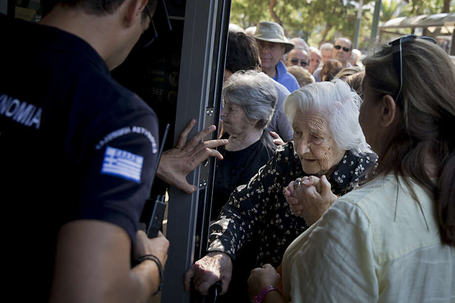 A Greek police man opens the door as an elderly woman with the help of her daughter enters a bank in Athens, on Wednesday, July 1, 2015, to withdraw a maximum 120 euros for the week, during capital controls in Greece. About 1,000 banks have been opened for three days across the country only for pensioners who don't have bank cards and so are completely cut off from their account. Pensions were being paid into people's accounts, although some were being paid late or only half the amount was being credited. (AP Photo/Petros Giannakouris)