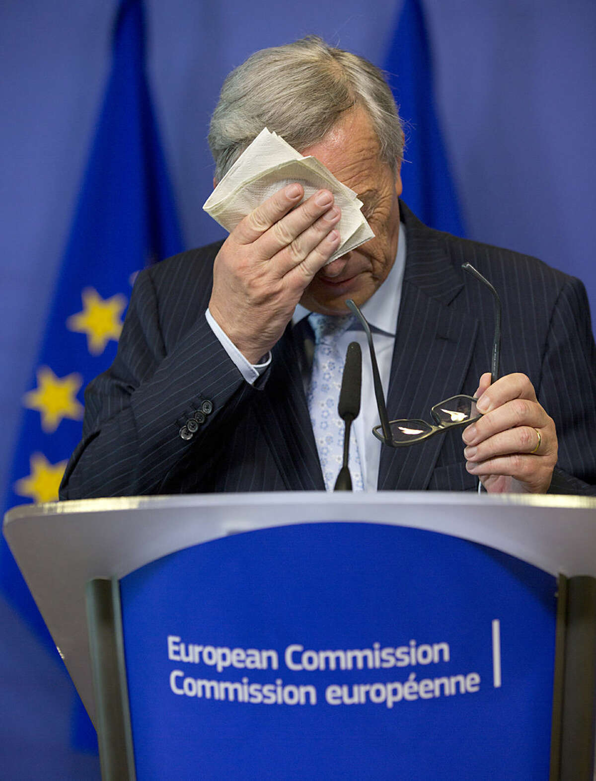 European Commission President Jean-Claude Juncker wipes his face before speaking during a media conference at EU headquarters in Brussels on Wednesday, July 1, 2015. The eurozone's finance ministers are set to weigh a last-minute Greek proposal for a new aid program, submitted Tuesday afternoon, in a conference call which will take place later on Wednesday. (AP Photo/Virginia Mayo)