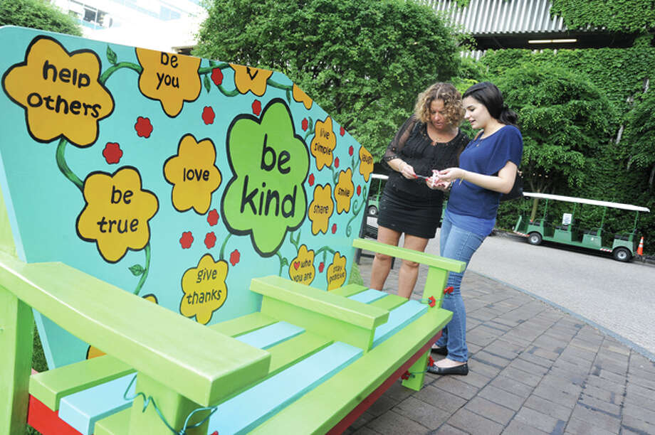 Taryn Pelli and Sabrini Taylor admire the Be Kind and Recline art bench in front of the Stamford Marriott Hotel in Spa. The bench is part of the Street Seats in Stamford Downtown, an interactive outdoor sculpture exhibit, which consists of 40 originally designed and painted wooden benches throughout Stamford Downtown and at the Stamford Town Center. The benches will be on display all summer.