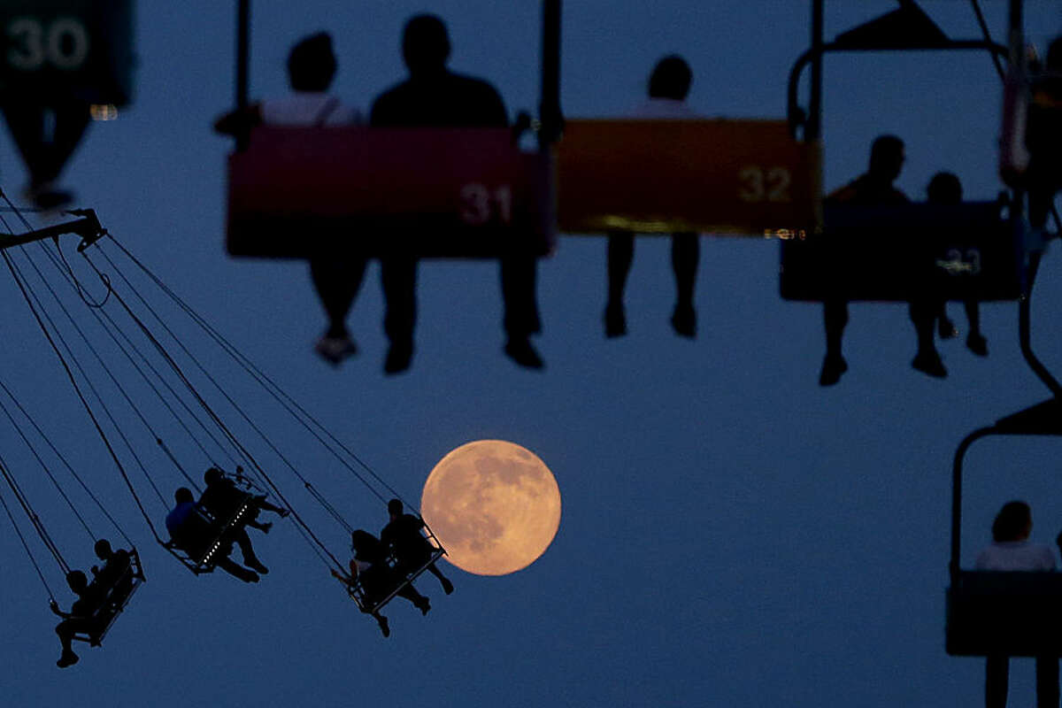 The moon rises as people sit on rides at the State Fair Meadowlands, Wednesday, July 1, 2015, in East Rutherford, N.J. The fair closes on Sunday. (AP Photo/Julio Cortez)