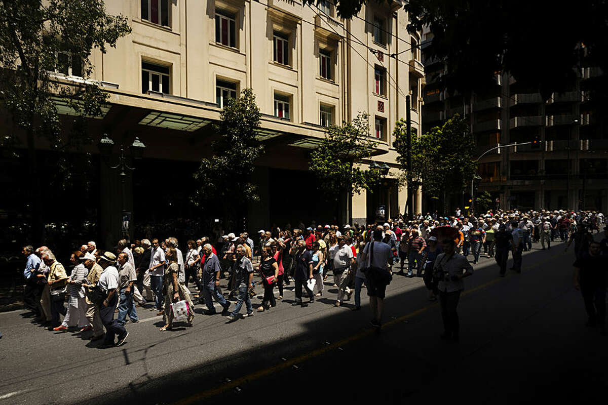 Elderly people march demanding their entire pensions during a protest in Athens, Wednesday, July 1, 2015. Crowds of anxious elderly Greeks thronged banks for hours from before dawn Wednesday, struggling to be allowed to withdraw their maximum of 120 euros ($134) for the week, after Greece reopened some banks to help pensioners who don't have bank cards. (AP Photo/Daniel Ochoa de Olza)