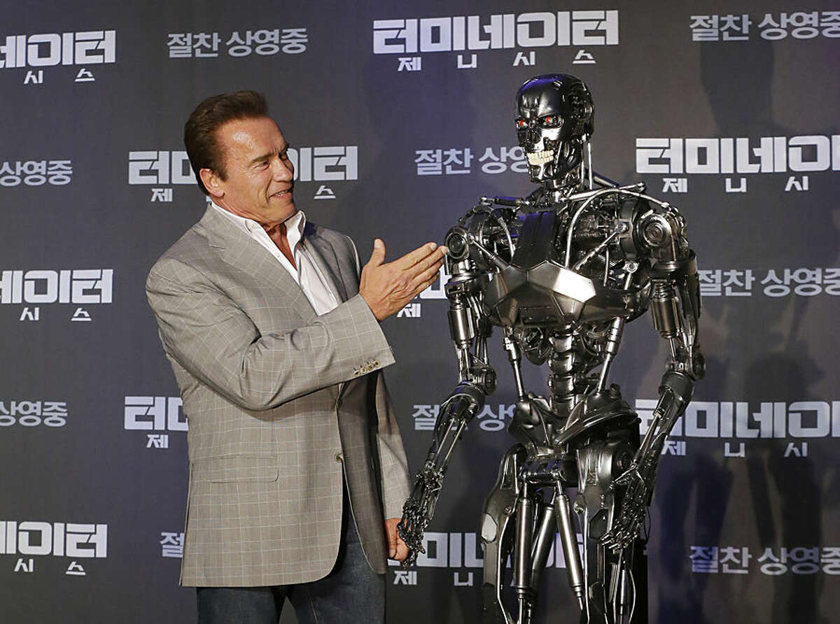 Actor Arnold Schwarzenegger stands with a model of a