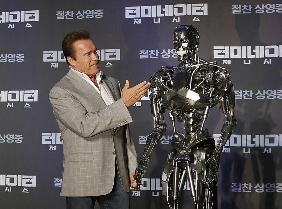 "Actor Arnold Schwarzenegger stands with a model of a ""Terminator"" from the new film ""Terminator Genisys"" during a press conference at the Ritz Carlton hotel in Seoul, South Korea, Thursday, July 2, 2015. (AP Photo/Ahn Young-joon)"