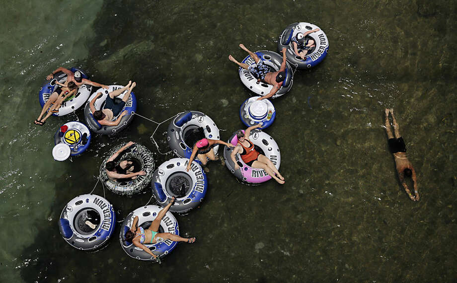 Tubers float on the Comal River, Wednesday, July 1, 2015, in New Braunfels, Texas. Both the Comal, with was closed briefly Tuesday due to weather, and Guadalupe river, which has been closed to tubers for several weeks, are scheduled to be open for water recreation for the holiday weekend. (AP Photo/Eric Gay)
