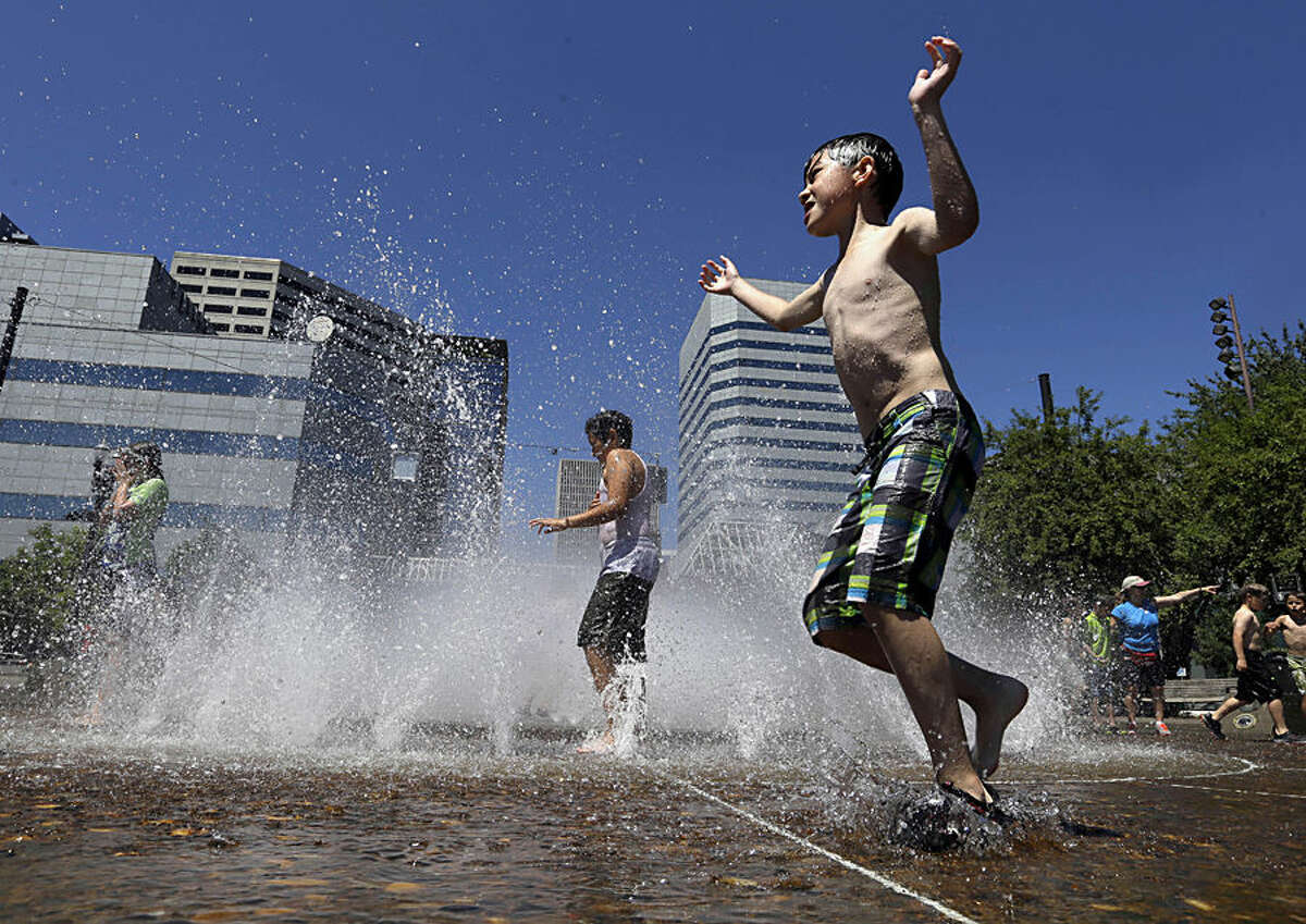 Children play in the Salmon Street Springs fountain in Portland, Ore., Wednesday, July 1, 2015. A heat advisory is in effect for Portland from noon Wednesday to 8 p.m. Thursday, according to the national weather service. (AP Photo/Don Ryan)