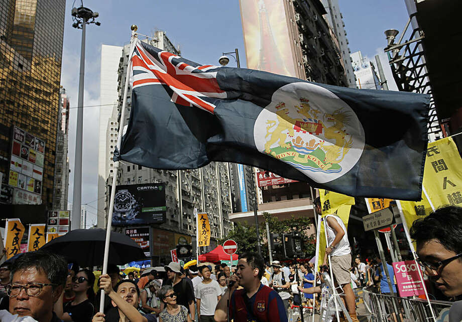 A protester raises a Hong Kong colonial flag during an annual pro-democracy protest in Hong Kong, Wednesday, July 1, 2015. Thousands of Hong Kongers in crowds noticeably smaller than previous years took to the streets Wednesday to renew their call for full democracy for the Asian financial hub in a rally that follows a turbulent year of protests over political reform. (AP Photo/Vincent Yu)