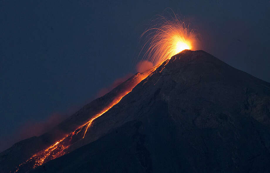 In this image taken with a long exposure, the Volcan de Fuego, or Volcano of Fire, spews hot molten lava from its crater in San Juan Alotenango, Guatemala, Wednesday, July 1, 2015. The Guatemalan emergency agency CONRED raised the alert level in the area after the volcano restarted its activity on early Wednesday. (AP Photo/Moises Castillo)
