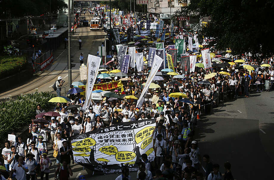 Pro-democracy protesters march during an annual protest marking Hong Kong's handover from British to Chinese rule in 1997 in Hong Kong, Wednesday, July 1, 2015. Thousands of Hong Kongers in crowds noticeably smaller than previous years took to the streets Wednesday to renew their call for full democracy for the Asian financial hub in a rally that follows a turbulent year of protests over political reform.(AP Photo/Kin Cheung)