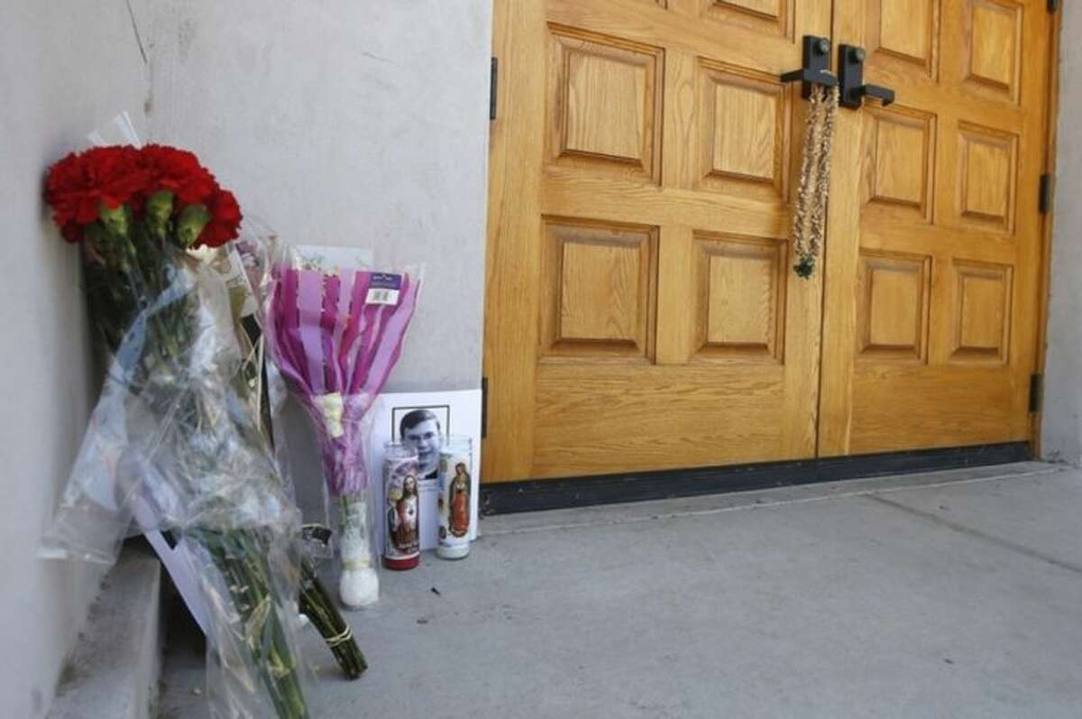 A makeshift memorial is set up for the Rev. Kenneth Walker, at the Roman Catholic church the Mother of Mercy Mission on Thursday, June 12, 2014, in Phoenix, after a Wednesday evening attack left Walker shot and killed and the Rev. Joseph Terra critically injured. Police have no suspects at this point, but they are canvassing the neighborhood and going over physical evidence from the scene. (AP Photo/Ross D. Franklin)