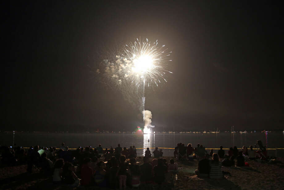 Hour photo/Danielle Calloway People gather on the beach to watch the annual Stamford fireworks display at Cummings Park Thursday evening.