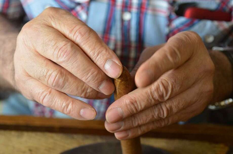Hour Photo/Alex von Kleydorff The hands of Master Cigar Roller Alberto Hernandez Cruz as he crafts a hand made cigar with tobacco from Nicaragua