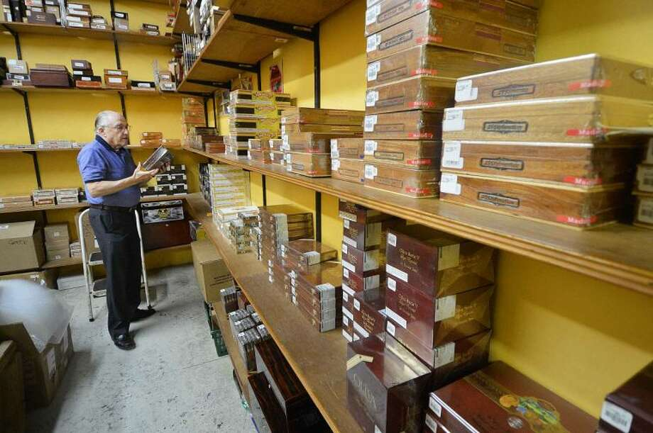 Hour Photo/Alex von Kleydorff Owner Ron Shapiro grabs a box of Olivia cigars form the shipping room