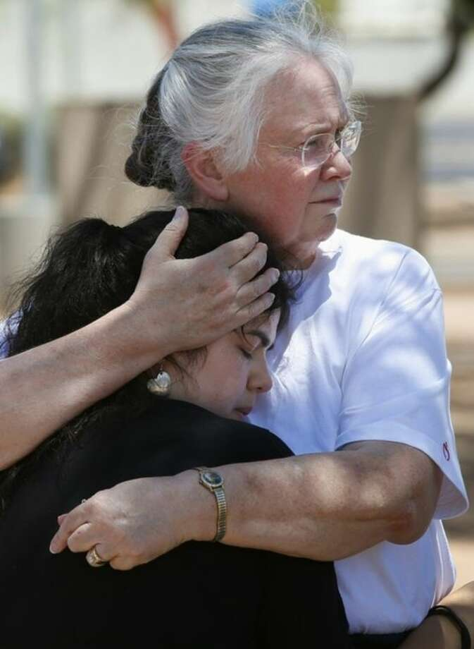 Marsha Livingston, right, comforts a grieving Kristen Williams, both parishioners at Mother of Mercy church, as they stand outside the church on Thursday, June 12, 2014, in Phoenix, after a Wednesday evening attack left a priest shot and killed and another injured at the Roman Catholic church. Police have no suspects at this point, but they are canvassing the neighborhood and going over physical evidence from the scene. (AP Photo/Ross D. Franklin)