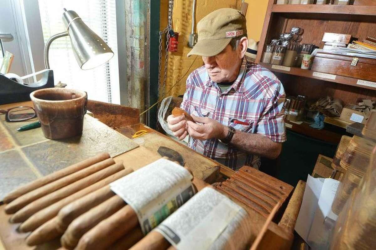 Hour Photo/Alex von Kleydorff Master Cigar Roller Alberto Hernandz Cruz works on placing a wrapper on a hand made cigar for customers at International Cigar Factory outlet