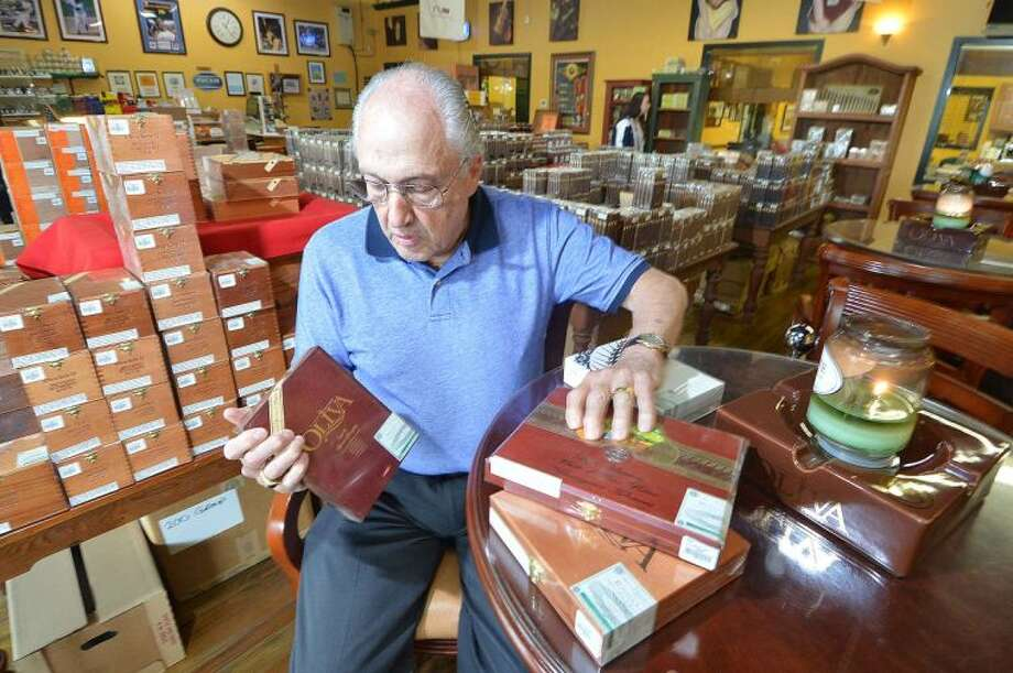 Hour Photo/Alex von Kleydorff Ron Shapiro , Owner of International Cigar Facory Outlet places some of the boxes of cigars for Fathers day, on a table near the lounge area and showroom in his Hanford Place store . Since 1932 the family run business stocks hundreds of different types of cigars along with Humidors, accesories and all things related, and can ship anywhere