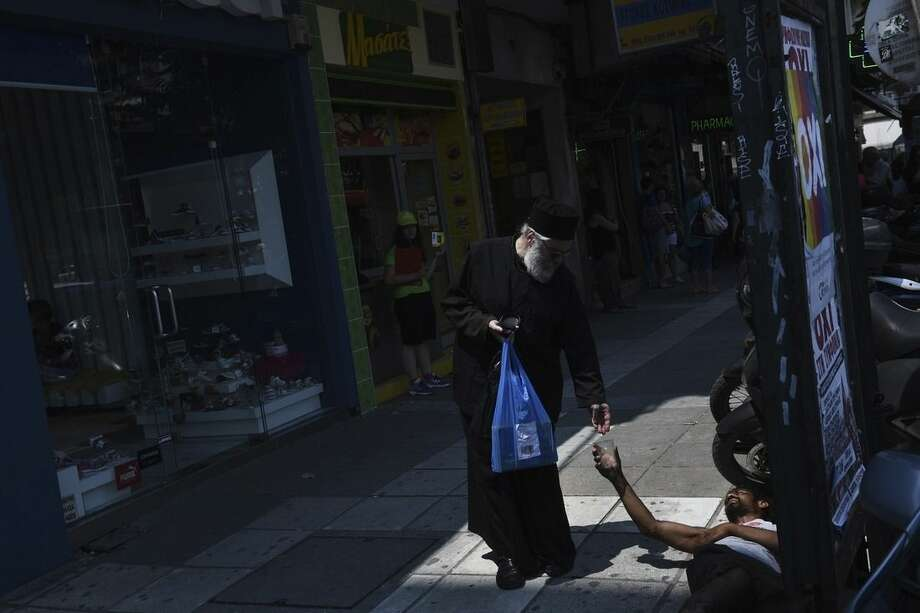 "A Greek Orthodox priest gives money to a man who begs for alms under a banner reading ""No"" referring to the upcoming referendum in the northern Greek port city of Thessaloniki Friday, July 3, 2015. Greeks will vote Sunday on whether to accept a proposal that creditors had made of specific reforms in exchange for loans. European Union institutions are framing it as a vote for or against the euro. (AP Photo/Giannis Papanikos)"
