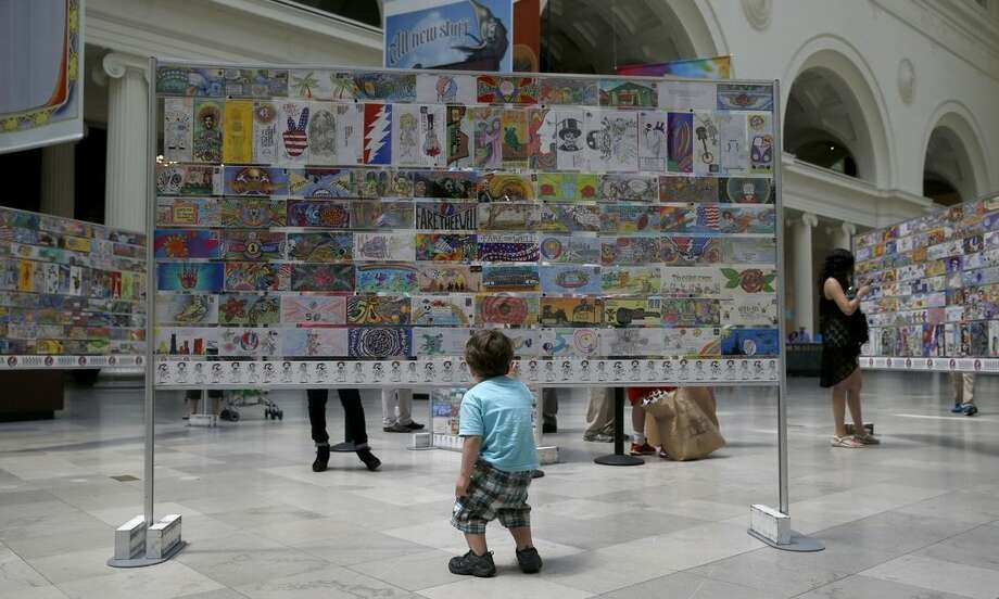 In this Tuesday, June 30, 2015, photo, Alex Kovacs, from Lafayette, Ind., walks around a display of decorative mailing envelopes, sent to the Grateful Dead's ticketing agent, by a fans seeking to purchase tickets to a future concert, at the Field Museum in Chicago. The Dead are scheduled to perform multiple shows over the July 4th weekend at Soldier Field. (AP Photo/Charles Rex Arbogast)