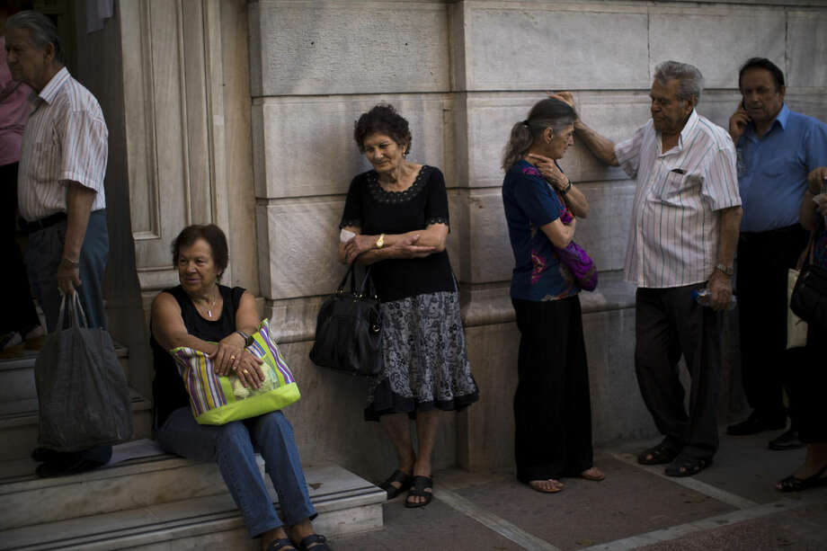 People wait to be allowed into the national bank of Greece to withdraw a maximum of 120 euros ($134) for the week, in central Athens, Friday, July 3, 2015. As Greek banks and markets remain closed Friday for a fifth day, rival campaigns scrambled to roll out their messages. And a prediction from the International Monetary Fund that Greece will need piles of additional cash from eurozone countries and others over the next three years put even more pressure on the government. (AP Photo/Emilio Morenatti)