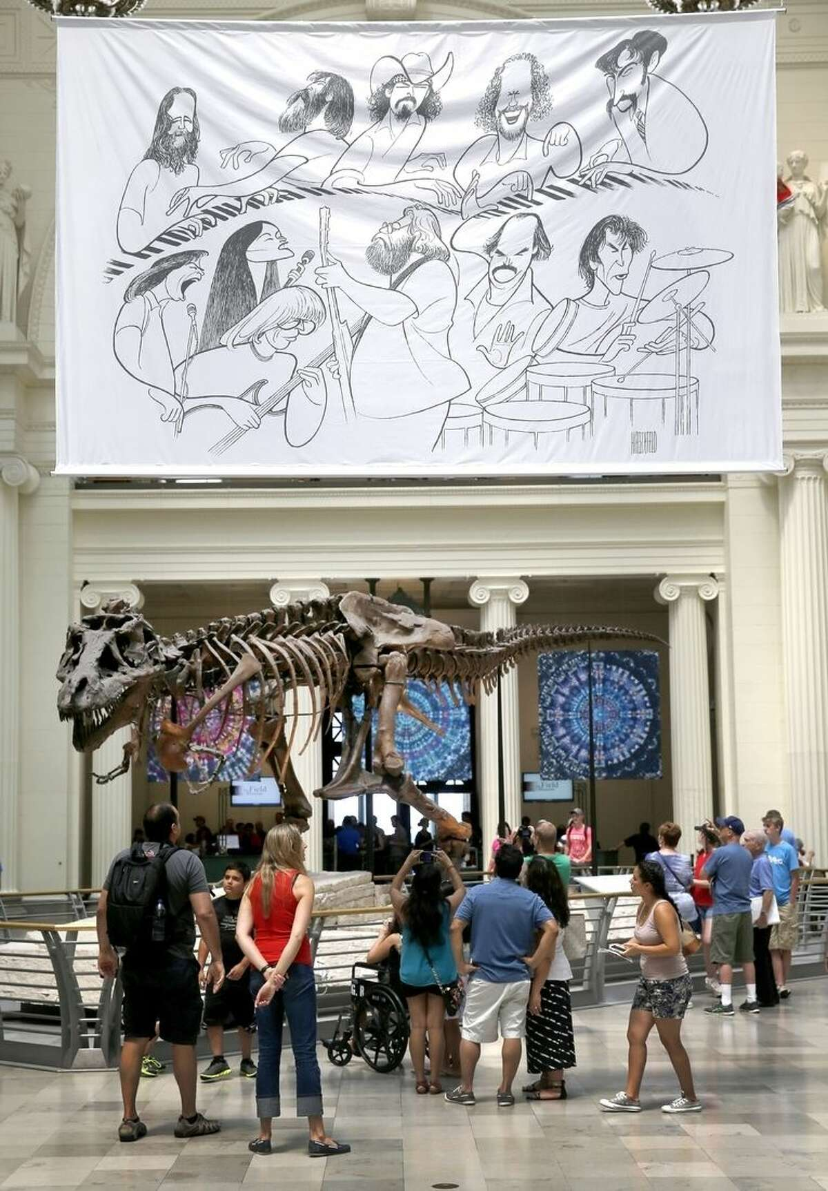 In this photo taken Tuesday, June 30, 2015, a banner of an Al Hirschfeld caricature of the Grateful Band members hangs over the Field Museum's famous Sue, the most extensive Tyrannosaurus rex specimen ever found, as part of a Dead exhibit in Chicago. The Dead will perform over the July 4th weekend at Soldier Field. (AP Photo/Charles Rex Arbogast)