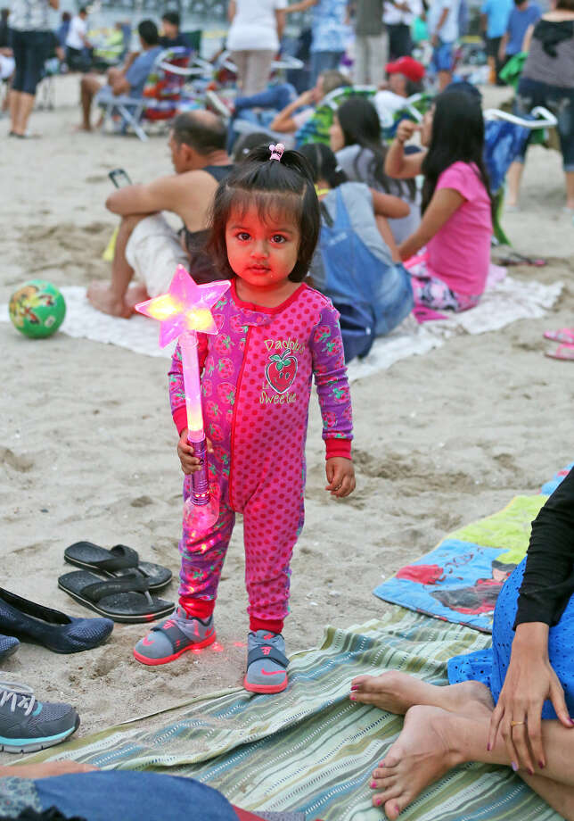 Aarya Patel, 20 months, plays with a toy before the annual Stamford fireworks display at Cummings Park Thursday evening. Hour Photo / Danielle Calloway