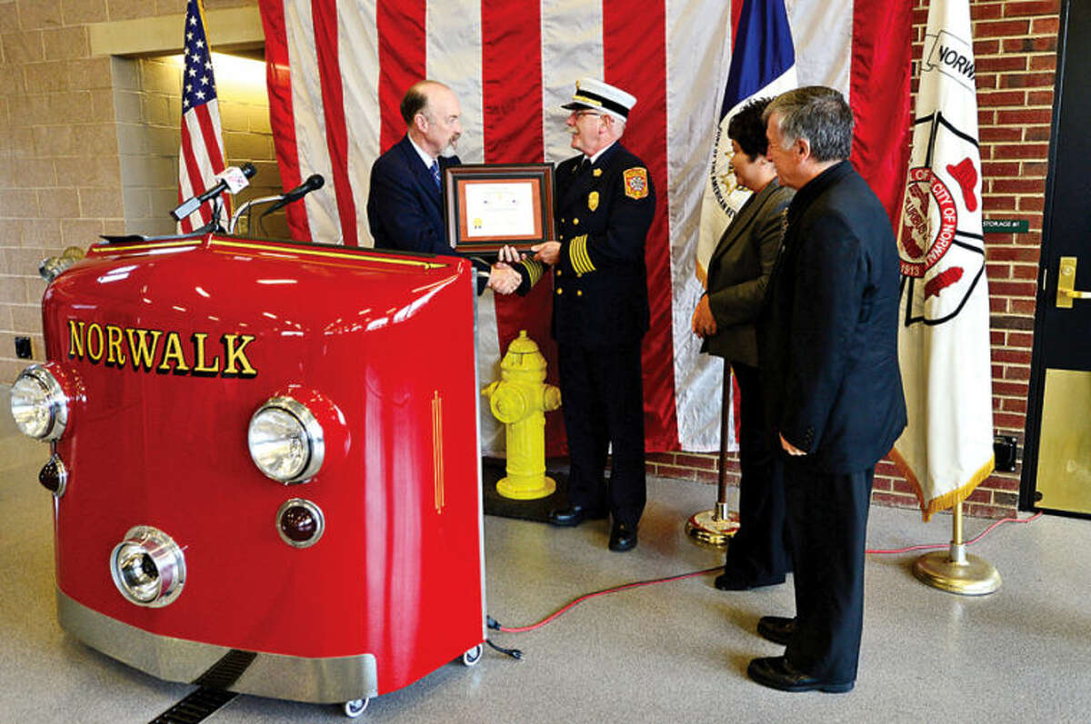 Hour photo / Erik Trautmann The Sons of the American Revolution Roger Sherman Branch president Harding Dies presents a certificate for the exemplary display of the American flag to the Fire Chief Denis MCarthy of the Norwalk Fire Department as fire commissioners Irene Dixon and Oscar Destruge look on during a ceremony at Fire Department Headquarters Friday.