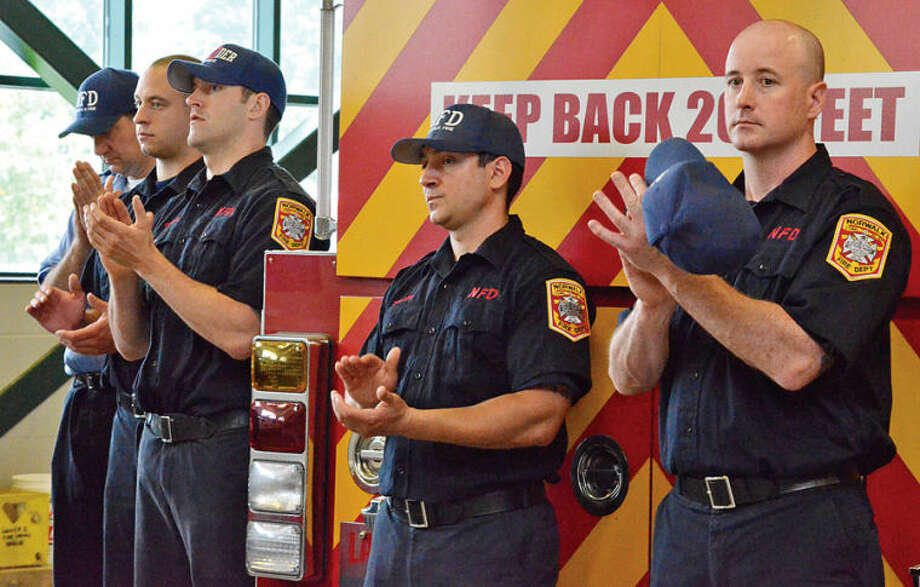 Norwalk firefighters applaud during a ceremony held Saturday at Norwalk Fire Department Headquarters in commemoration of Flag Day.