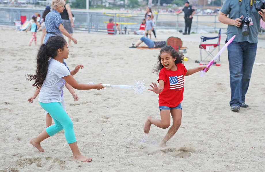 Kaydence Torrealba, 6, and Melody Lewis, 4, play on the sand before the annual Stamford fireworks display at Cummings Park Thursday evening. Hour Photo / Danielle Calloway