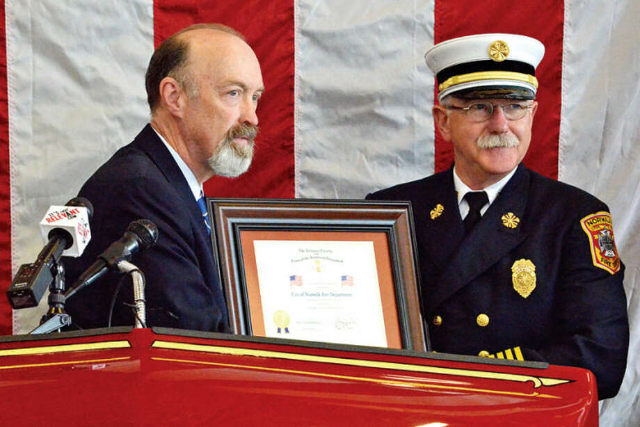 Hour photo / Liana Sonenclar Harding Dies presents a Certificate of Commendation to Fire Chief Denis McCarthy during a ceremony held Saturday at Norwalk Fire Department Headquarters in commemoration of Flag Day.