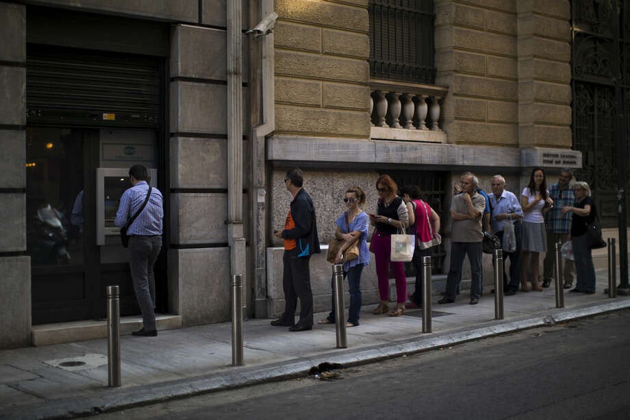 People line up to withdraw money from a bank machine in central Athens, Friday, July 3, 2015. As Greek banks and markets remain closed Friday for a fifth day, rival campaigns scrambled to roll out their messages. And a prediction from the International Monetary Fund that Greece will need piles of additional cash from eurozone countries and others over the next three years put even more pressure on the government. (AP Photo/Emilio Morenatti)