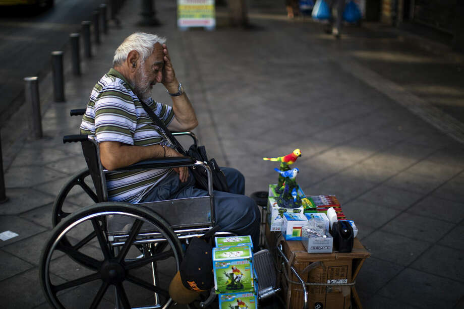 "A man on a wheel chair sells items in central Athens, Friday, July 3, 2015. Rival campaigns in Greece's bailout referendum end Friday, with rallies planned in Athens for ""Yes"" and ""No"" supporters - at the same time. (AP Photo/Emilio Morenatti)"