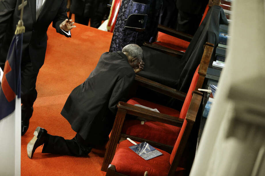 A parishioner prays at the empty seat of the Rev. Clementa Pinckney at the Emanuel A.M.E. Church four days after a mass shooting that claimed the lives of Pinckney and eight others on Sunday, June 21, 2015, in Charleston, S.C. (AP Photo/David Goldman, Pool)