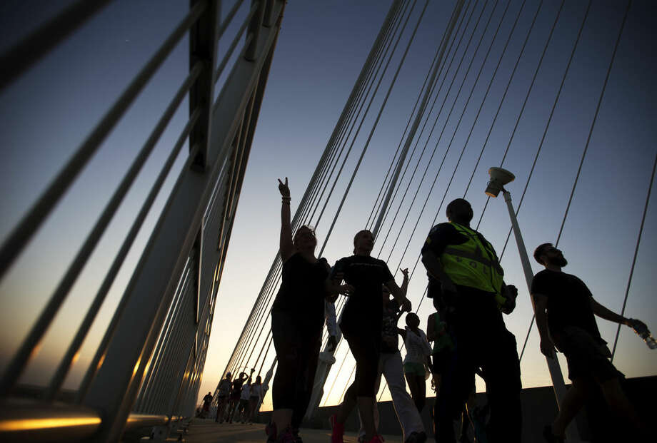 Marchers walk up Charleston's main bridge to meet in the middle in a show of unity after nine black church parishioners were gunned down during a Bible study, Sunday, June 21, 2015, in Charleston, S.C. (AP Photo/David Goldman)