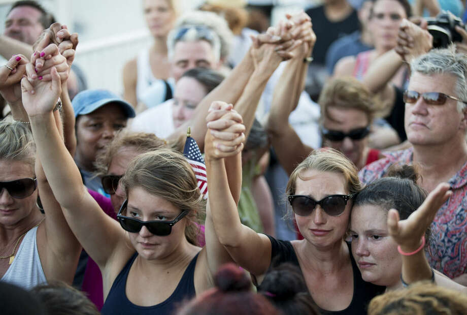 People join hands in a moment of silence as thousands of marchers meet in the middle of Charleston's main bridge in a show of unity after nine black church parishioners were gunned down during a Bible study, Sunday, June 21, 2015, in Charleston, S.C. (AP Photo/David Goldman)