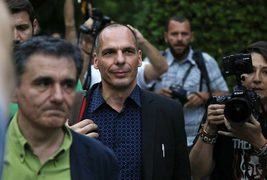 Greece's Finance Minister Yanis Varoufakis, center, and Deputy Foreign Minister for international economic relations, Euclid Tsakalotos, left, arrive for an urgent cabinet meeting at Maximos Mansion in Athens, Sunday, June 28, 2015. Greek Prime Minister Alexis Tsipras says the Bank of Greece has recommended that banks remain closed and restrictions be imposed on transactions, after the European Central Bank didn't increase the amount of emergency liquidity the lenders can access from the central bank. (AP Photo/Petros Karadjias)