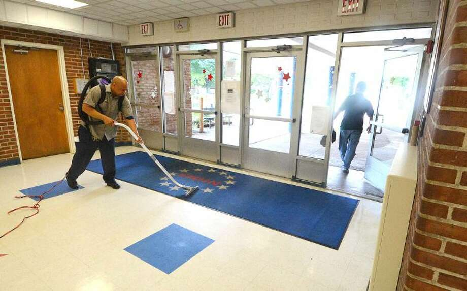 Hour Photo/Alex von Kleydorff As Teachers leave in the afternoon, Custodian Danny Thorne vacuums the rugs and cleans the glass doors and floors of the entrance foyer at Nathan Hale School