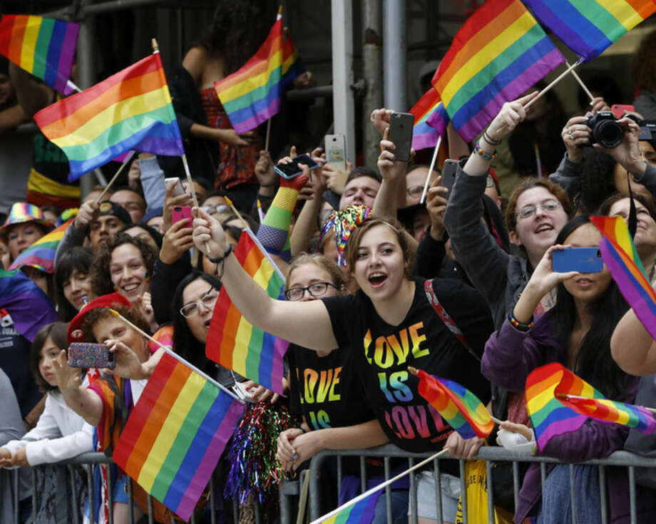 A crowd waves rainbow flags during the Heritage Pride March in New York, Sunday, June 28, 2015. Large turnouts were expected for gay pride parades across the U.S. following the landmark Supreme Court ruling that said gay couples can marry anywhere in the country. (AP Photo/Kathy Willens)